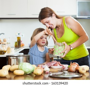 Happy mother with baby cooking with meat and vegetables
