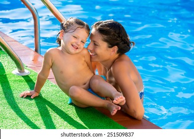 Happy mother and baby daughter girl at swimming pool in summer vacation