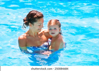 Happy mother and baby daughter at swimming pool in summer vacation