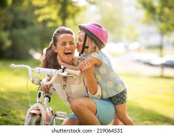 Happy mother and baby girl having fun in park with bicycle