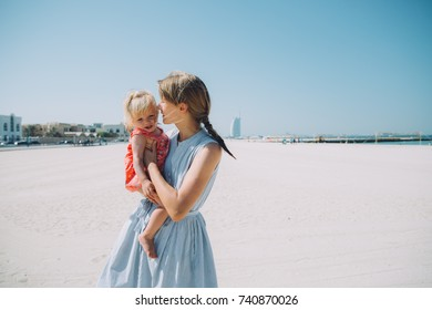 Happy mother and baby girl on the Kite beach in Dubai