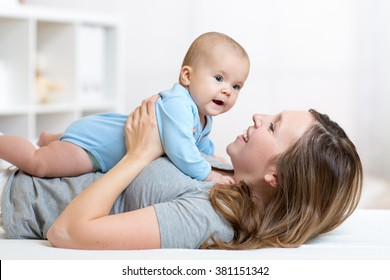 Happy mother and baby hug and play lying indoors
