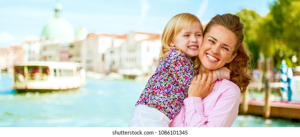 happy mother and baby hugging on grand canal embankment in venice, italy
