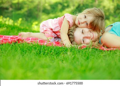 happy mother with baby in nature lying on the grass in the park