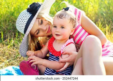 Happy mother with a baby in nature are resting