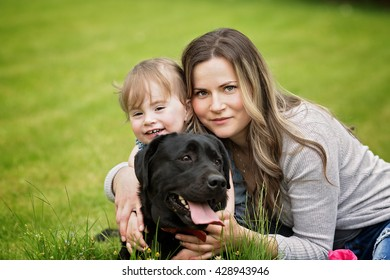 Happy mother with baby playing with dog in green field
