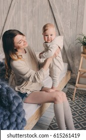 happy mother and baby playing at home in bedroom. Cozy family lifestyle in modern scandinavian interior.