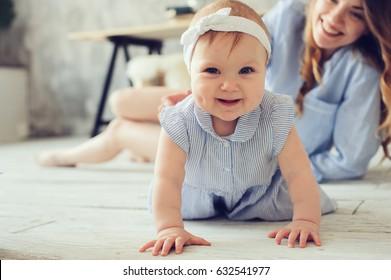 glückliche Mutter und Baby, die zu Hause im Schlafzimmer spielen. Gemütlicher familiärer Lebensstil im modernen skandinavischen Interieur.