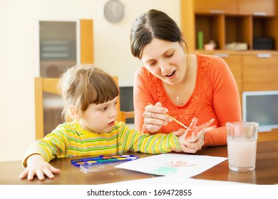 Happy mother and baby  plays with watercolor in home