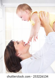 Happy mother and baby portrait, parents playing with a kid, having fun at home, healthy family enjoying life, parenting lifestyle