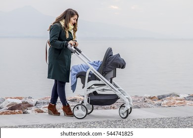 Happy Mother with Baby Stroller Walking near the sea shore and Enjoying Sunny Day. Sea and rocks Background. Happy Parenting and Healthy Lifestyle Concept. Photo with Copy Space.