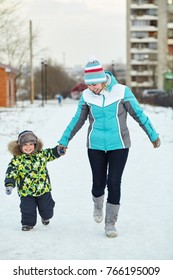 happy mother and baby walking in winter. family outdoors. cheerful mom with her child