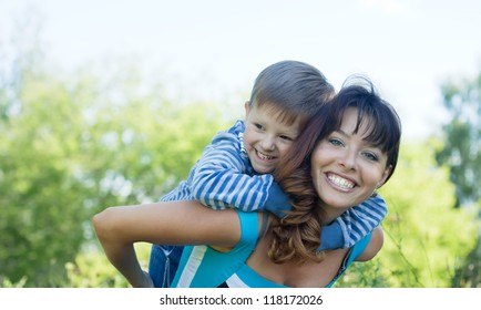 Happy mother with boy   against nature
