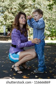 Happy mother with boy in autumn park