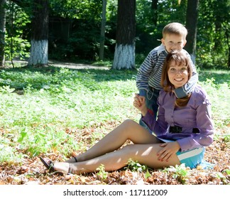 Happy mother with boy on grass in park
