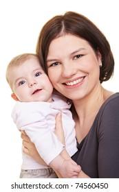 Happy mother carrying her baby girl in her hands