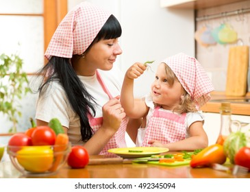 Happy mother and child daughter with salad n the kitchen