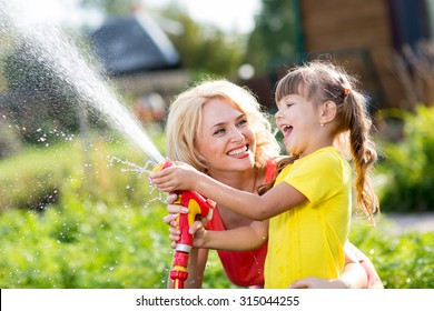 Happy mother and child daughter working in the garden