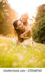 Happy mother with child enjoying together in sunny nature