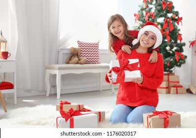 Happy mother and child with gifts celebrating Christmas at home