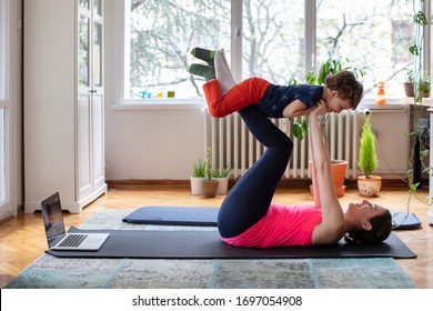 Happy Mother and Child Playing Flying Airplane with Joy while Exercising Pilates, Yoga, Fitness at Home in front of the Laptop