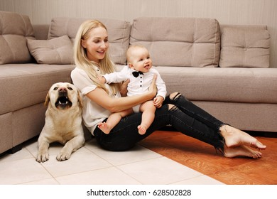 Happy mother with child playing with labrador in house near the couch