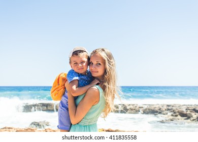 Happy mother with child son having fun outdoors in summer day