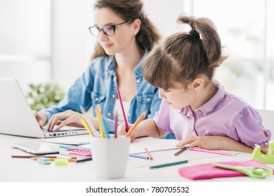 Happy mother and child spending time together at home, the woman is working with a laptop and the girl is drawing