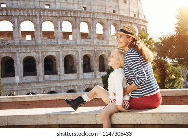 happy mother and child travellers in the front of Colosseum looking into the distance