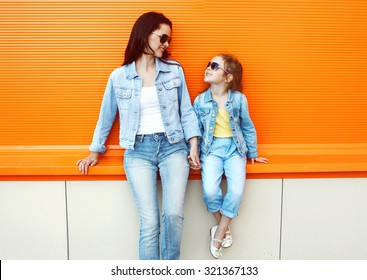 Happy mother and child wearing a jeans clothes in city