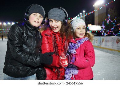 Happy mother with children make excellent gesture on the silent disco skating