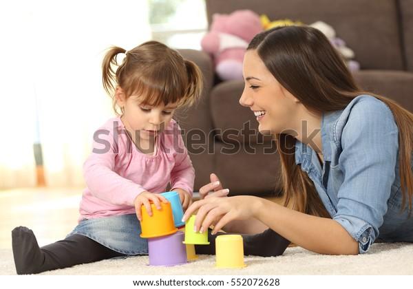 Madre felice e concentrato baby figlia giocare con giocattoli insieme seduti sul pavimento del soggiorno a casa