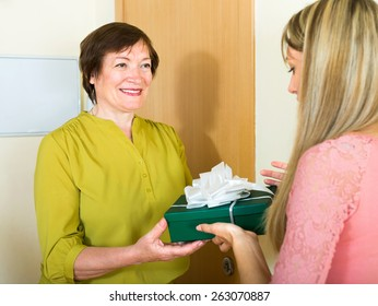 Happy mother congratulating adult daughter on birthday and giving her a gift