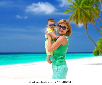 Happy mother with cute baby boy having tropical vacation on Maldives