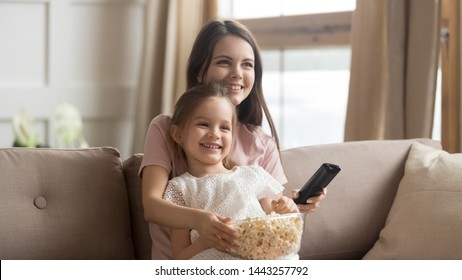Happy mother with cute little daughter watching tv, eating popcorn snack, using remote controller, sitting on couch together, having fun, cute preschool girl sitting on smiling mum knees at home