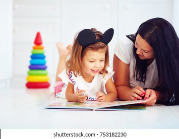 happy mother and daughter, baby girl reading book at home