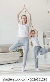 happy mother and daughter balancing in tree pose together