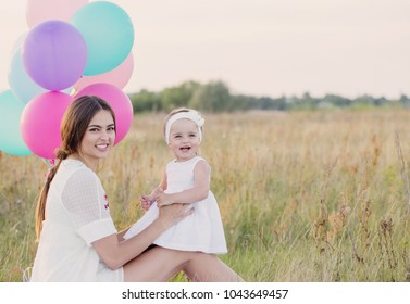 happy mother and daughter with balloons outdoor