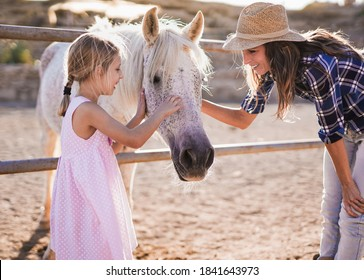 Happy mother and daughter caress horse outdoor on a ranch - Mom and child -  Animal love