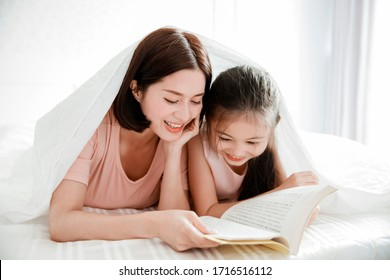 happy mother and  daughter child reading book together in bed