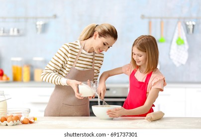 Happy mother and daughter cooking in light kitchen