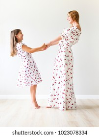 Happy mother and daughter dance together holding hands
