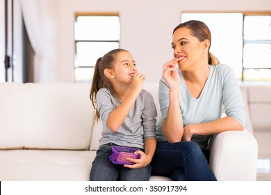 happy mother and daughter eating crackers at home