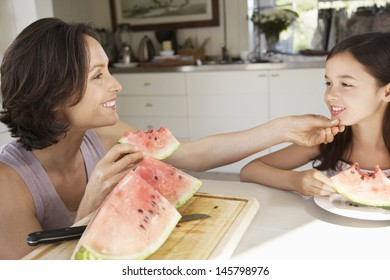 Happy mother and daughter eating watermelon at kitchen table