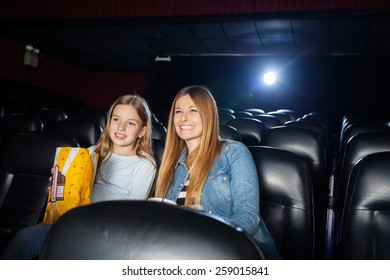 Happy mother and daughter enjoying film in movie theater