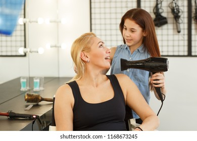 Happy mother and daughter enjoying playing together. Cute little girl blowdrying hair of her cheerful beautiful mom. Gorgeous mature woman smiling while her daughter styling her hair