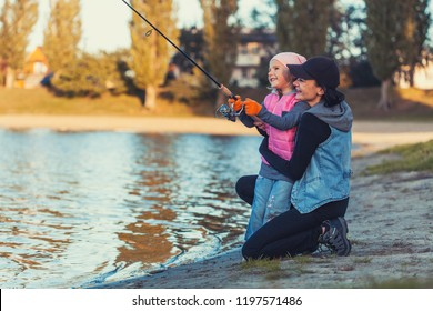 happy mother and daughter are fishing on the lake. Family activities