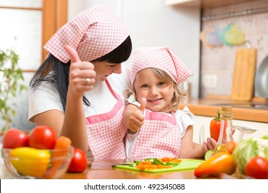 Happy mother and daughter with fresh vegetables showing thumbs up gesture. Shot in the kitchen