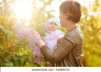 Happy mother and daughter in the garden of blooming lilacs
