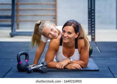 glückliche Mutter und Tochter im Fitnessraum, um Sport zu treiben
